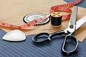Still life photo of bespoke suit making equipment including tape, chalk, thread, scissors and pins o