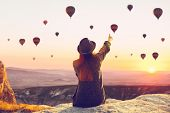 A Woman Alone Unplugged Sits On Top Of A Mountain And Admires The Flight Of Hot Air Balloons In Capp poster