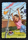 A stamp printed in Australia shows a girl playing on a clothesline as a hills hoist inventive