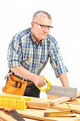 Carpenter cutting wooden batten with a saw isolated on white background
