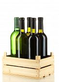 Wine bottles in wooden box isolated on white