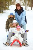 Happy kids and their parents tobogganing in park
