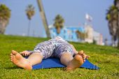 picture of corpses  - Woman in the park doing the corpse yoga pose during noon time. Focus is on the feet.
