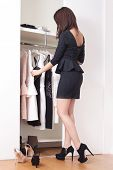 young elegant woman in front of open closet full of elegant dresses choose what to wear full body sh