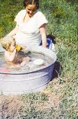 Vintage photo of pregnant mother and daughter bathing in a washtub (1981)