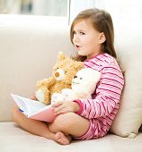 Little girl is reading a story for her teddy bears while laying in bed and wearing pajama, indoor sh