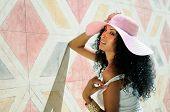 Joven negro a mujer vestida con vestido y sombrero para el sol, peinado Afro