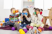 foto of daycare  - Cute kids playing in the room with toys - JPG