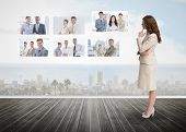 stock photo of stare  - Businesswoman staring at futuristic interface showing partners - JPG
