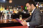 Attractive businessman sitting at bar reading drinks menu