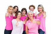 Positive women posing and wearing pink for breast cancer on white background