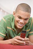 Teenage Boy Lying On Bed Using Mobile Phone