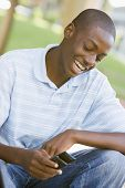 Teenage Boy Sitting Outdoors Using Mobile Phone