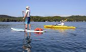 Man On Paddleboard Woman On Kayak