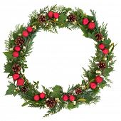 Christmas wreath with red baubles,  holly, mistletoe, ivy, pine cones and cedar leaf sprigs over white background.