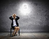 Image of depressed businesswoman sitting on chair with dollar sign above