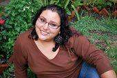 Beautiful Hispanic Woman Sitting Outside In The Grass