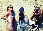 urban girls have fun with vintage photo cameras outdoor near grunge wall, image toned and noise adde