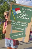 Young Woman Holds A Moral Monday Rally, North Carolina Discrimination Sign