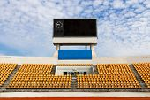 pic of lawn chair  - Rows of orange seats on the stadium with scoreboard displaying clock above them - JPG