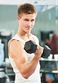 bodybuilder man at biceps brachii muscles exercises with training dumbbells in fitness gym