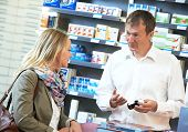 cheerful pharmacist chemist man worker standing at pharmacy drugstore desk with colleague