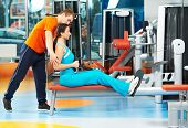 woman with training and equipment simulator doing exercises for back muscles at fitness club gym
