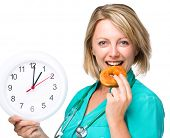 Young happy lady wearing doctor uniform is biting donut while holding big clock, lunchtime concept, isolated over white