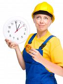 Young happy lady as a construction worker is biting donut while holding big clock, lunchtime concept, isolated over white