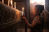 Old wrinkled traditional Asian woman praying with candle light inside a temple, low light, Myanmar