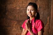 stock photo of polite girl  - Myanmar girl in a traditional welcoming gesture - JPG