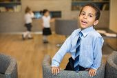 Little mulatto boy in a shirt and tie in a business center with girls on the background