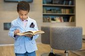 Little mulatto boy in a striped jacket read a book in library