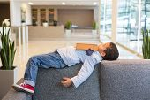 Curly boy in a shirt and jeans sleeps with the book on a sofa in a business center