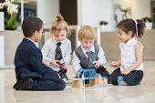 Four children in business dress playing with toys in the business center