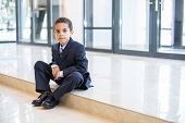 Mulatto little boy in a suit sitting in front of the business center