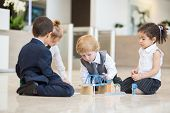 Four children in business dress playing with toys on the floor in business center