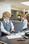 Little boy and girl in business suit playing with stationery in a business center, boy uses a puncher