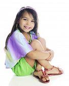 A beautiful young elementary girl with long, brown hair sitting with her arms wrapped around her leg