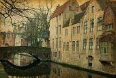 One of Bruges' canals, Belgium. Photo in retro style. Added paper texture.