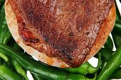 meaty food : grilled red meat steak over arabic pita on a green hot chili peppers on a white back background