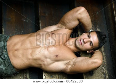 Attractive Muscular Young Man Laying On Steps Of Wooden Stair poster