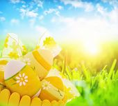 Easter eggs in the basket on fresh grass meadow, bright sun shine, eggs painted with yellow colours and floral ornament, traditional religious symbol for Eastertime