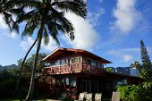 Red Two Story Beach House With Tall Coconut Trees