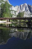 Wooden footbridge over the Merced River in Yosemite Park. In the still water reflected the famous ro