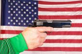 close-up of a man's hand holding a semi-automatic pistol in front of an American flag