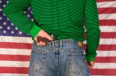Man standing in front of a US flag holding the grip of a handgun which is stuck behind his back in his pants
