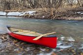 red canoe with a wooden paddle on river shore in winter or early spring - Cache la Poudre River, For