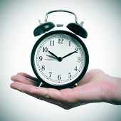 picture of daylight saving time  - someone holding an alarm clock adjusting forward one hour for the summer time - JPG