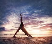 picture of ashtanga vinyasa yoga  - Man doing Yoga on the beach near the ocean in India - JPG